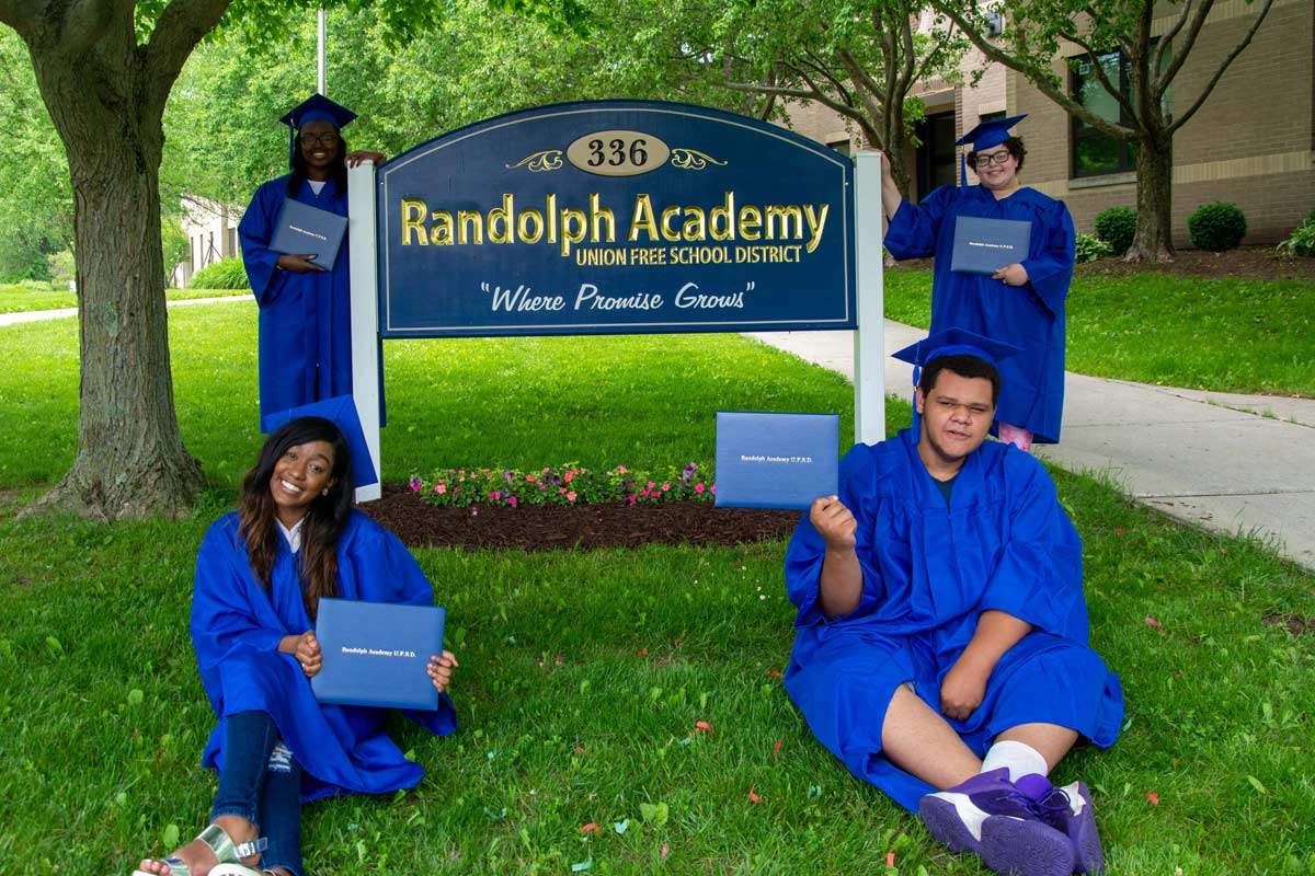 grads pose in front of school sign