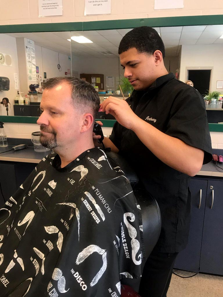 student carefully shapes with a trimmer