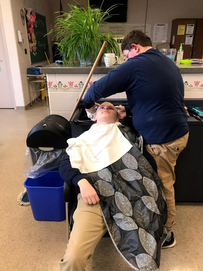 student washes hair of barbering client